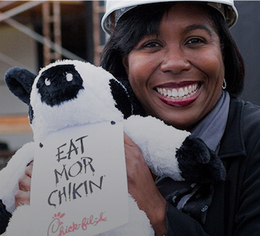 Woman in construction hat holds a Chick-fil-A cow